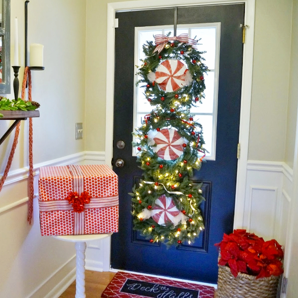 Front door decorated with a triple wreath for Christmas